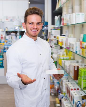 Ordinary man pharmacist wearing white coat standing among shelves in drug store Imagens