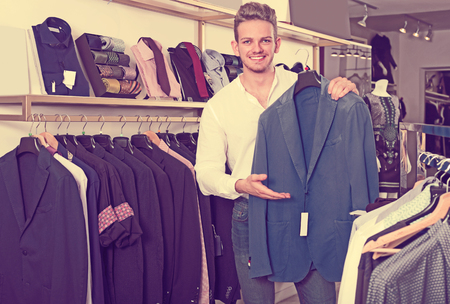 Young man purchasing jacket at clothing shop Stock Photo