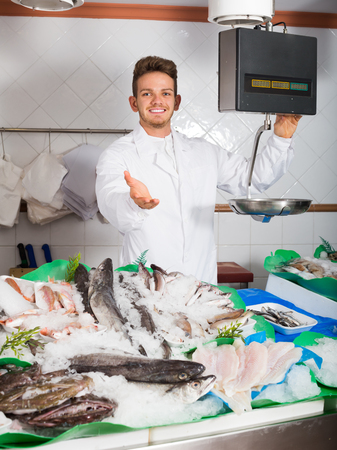 Glad guy selling chilled fish and seafood in store Фото со стока