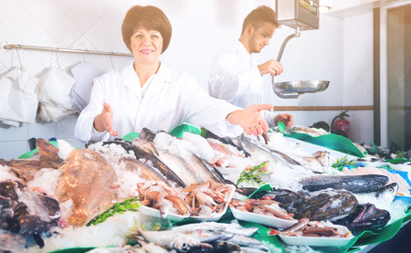 Woman seller and assistant offering fresh fish in shop