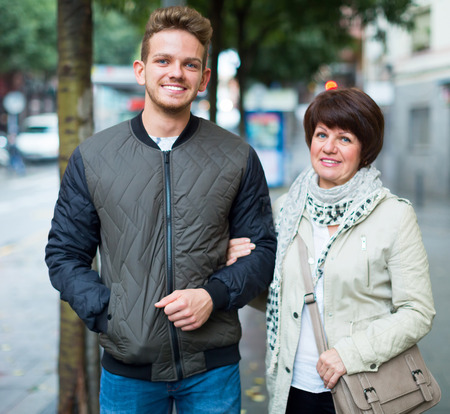 Mature woman and guy taking walk in city at summer day