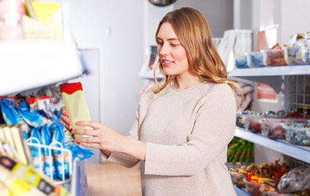 Portrait of  woman customer choosing spices in  grocery food shop