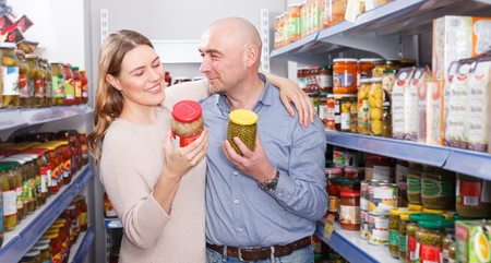 Portrait of woman and man   holding pickle goods  in the hypermarket