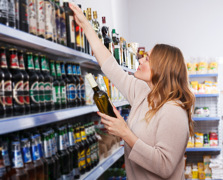 Portrait of female customer buying bottle of wine in the shop