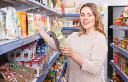 Adult positive woman buyer with assortment of grocery food store