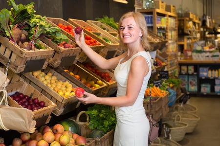 cheerful female customer picking fresh  fruits in food shop Stok Fotoğraf