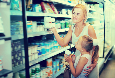 Portrait of adult woman and girl holding yogurt in grocery shop Stok Fotoğraf
