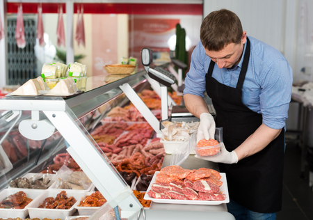 Professional butcher arranging meat products in display case of butcher shop Фото со стока