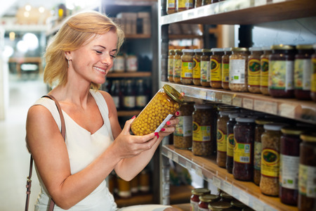 Cheerful female customer choosing preserve peas in jar at a food shop  Stok Fotoğraf