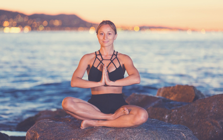 Young woman is meditating on a rock near sea at the dawn.
