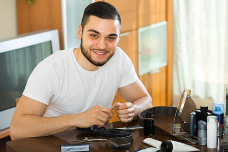 Young smiling guy cutting nails with cuticle scissors