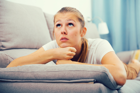 Sad woman is propped her cheeks with hands because she bored at home.