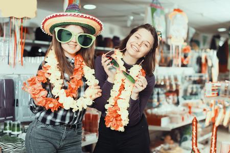 Portrait of friendly comically dressed girls joking in festive accessories shop Reklamní fotografie