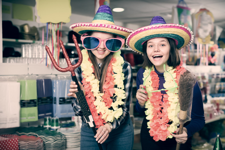 Portrait of happy young comically dressed girls joking in festive accessories shop Reklamní fotografie