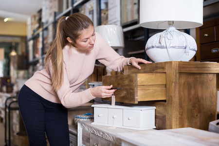 Woman buyer standing in furniture shopping room near chest of drawers Zdjęcie Seryjne