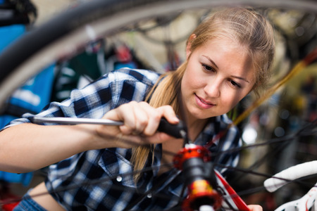 Young woman master is fixing wheel of bicycle in bicycle service Фото со стока