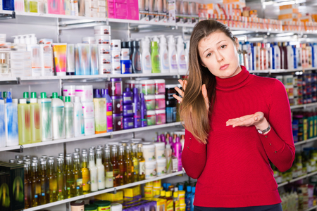 Portrait of upset unhappy angry woman who is dissatisfied of quality her hair in the store.