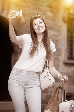 Smiling female tourist making selfie on the background of landmark