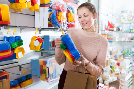 Young female consumer  buying plastic toys in the kids store