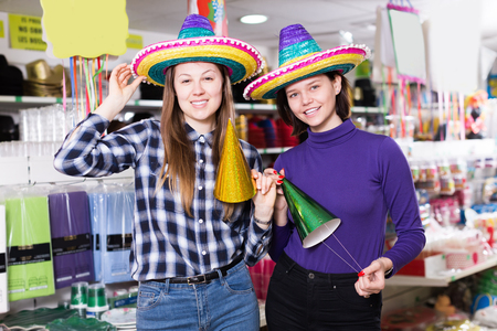 Two playfully girls in colorful party hats in festive decoration shop Archivio Fotografico