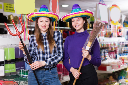 Comically dressed happy female friends having fun in festival outfits shop Reklamní fotografie