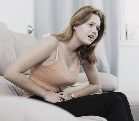 Portrait of ill young female with pain in stomach on sofa indoors