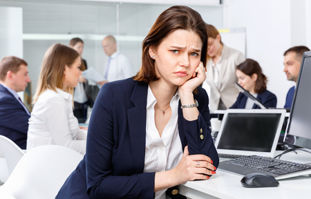 Portrait of angry unhappy girl in modern open plan office on background with coworkers
