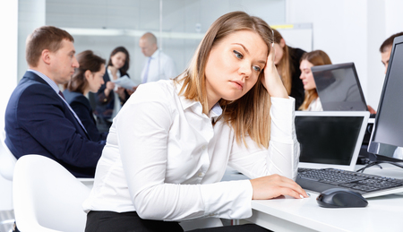 Portrait of pleasant  angry unhappy girl in modern open plan office on background with coworkers