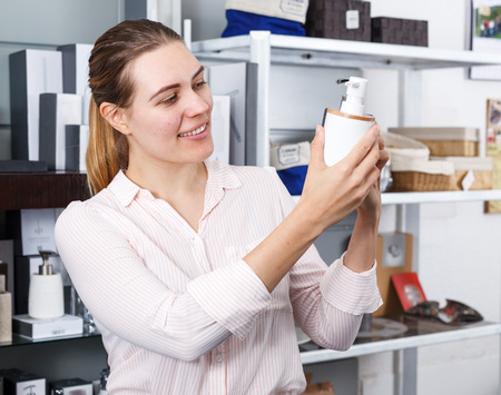 Young woman choosing bottle for  liquid soap for home in  supermarket