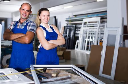 Portrait de deux ouvriers travaillant dans un atelier de production de fenêtres en plastique.