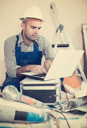 builder directs the repair process while sitting behind a laptop