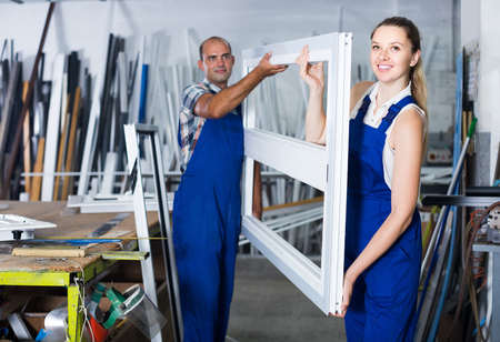 Two germany  professional workers working in assembly shop of plastic windows