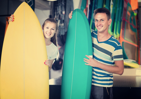 Smiling american couple is demonstraiting surfboard in nautical shop.