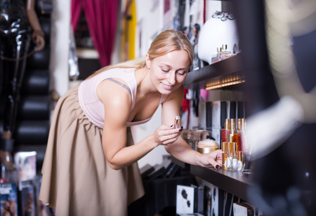 Woman customer shopping pheromones perfume in store for adults