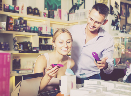 excited young adult couple selecting erotic toys in sex shop. Focus on woman Standard-Bild - 102121720