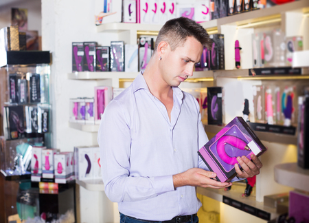 Portrait of positive man choosing erotic toys in sex shop Imagens