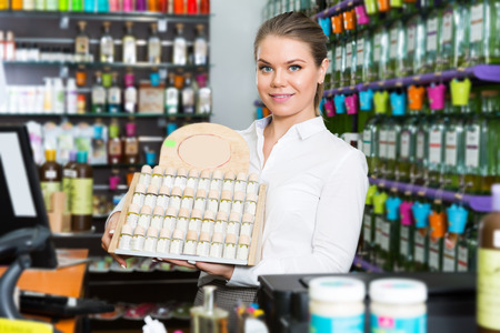 Young happy saleswoman working behind counter in perfume shop Stock Photo
