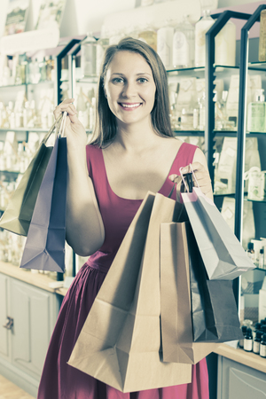 Smiling woman displaying shopping bags with purchase in natural cosmetics store