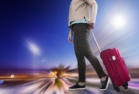 Girl walking with suitcase on wheels before boarding to plane