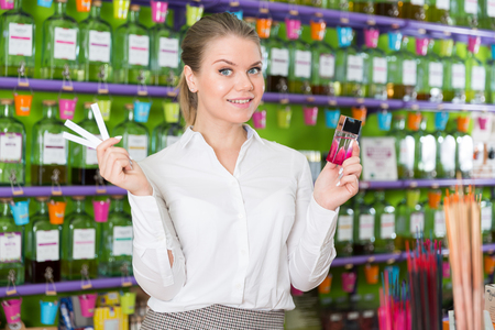 Young woman looking for stylish fragrance of perfume in cosmetic shop Banque d'images