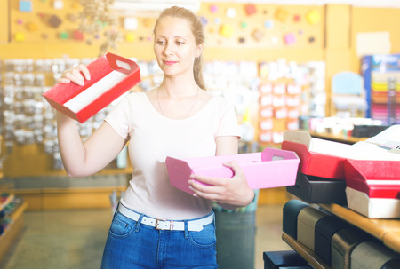 Female is choosing red or pink palettes for trifle in store.  Stock Photo