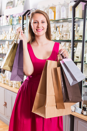 Happy woman displaying shopping bags with purchase in natural cosmetics shop