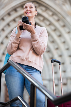 Young girl holding camera in hands and photographing in the city