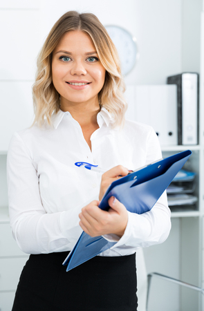 Young girl with folder of documents is standing in modern office