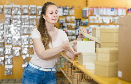 Cheerful housewife choosing new gift boxes at shop Stock Photo