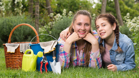 smiling young american woman and girl with gardening tools in outdoors Standard-Bild