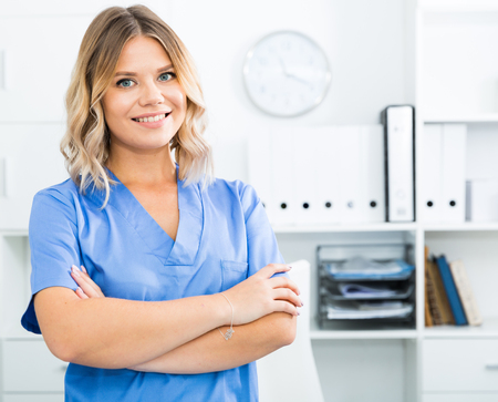 Doctor girl stands near a table in the office Фото со стока