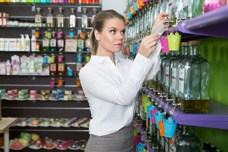 Young saleswoman offering perfume on tap in modern perfumery