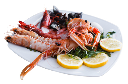 Delicious prawns, langoustines and clams served with arugula and lemon on white plate on wooden surface