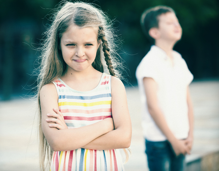 portrait of angry girl in elementary school age not playing with friend in park outdoors Stock Photo